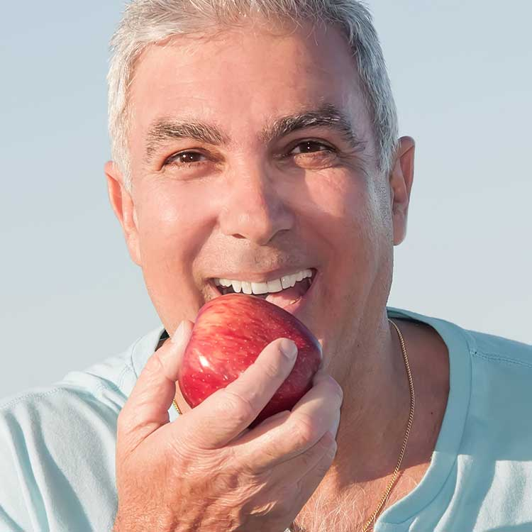 Man having apple after Dentures Wagga